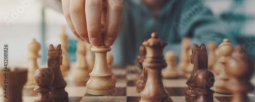 Fotografija Boy playing chess and moving a piece