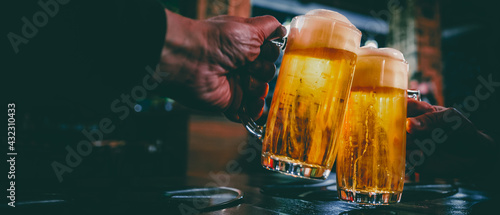 фотография Close-up view of a two glass of beer in hand