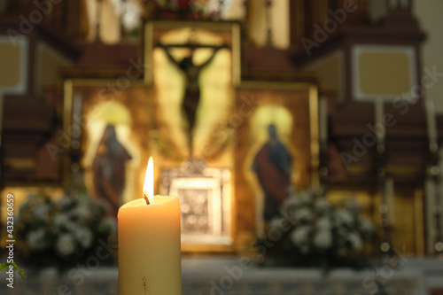 Lighted candle with a catholic altarpiece on the bottom with a crucified christ Fototapete