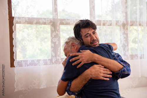Photo Caucasian senior father comforting and hugging depressed adult son in the bedroom
