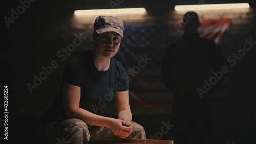 Photo Female soldier sitting near anonymous commander