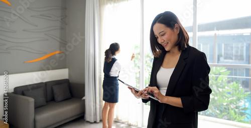 Fotografiet Asian businesswoman in black suit standing with tablet computer in her hand