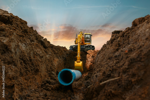Fototapeta Excavator is digging in the construction site pipeline work on sunset sky backgr