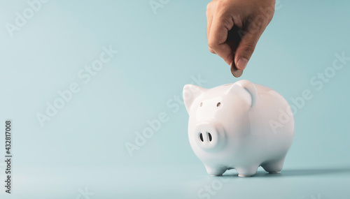 Fotografering Hand putting coin to white piggy saving bank on blue background, Financial money and bank deposit for investment concept