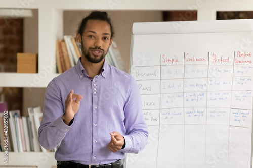 Photo Head shot portrait African American man teacher recording webinar, explaining, s