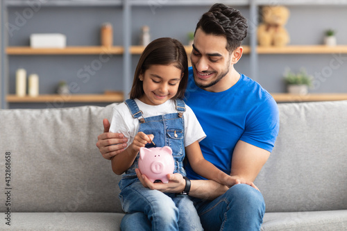 Photo Little girl and dad saving money in piggy bank