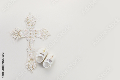 Leinwand Poster Christening background with baptism baby shoes, and cross on pastel background