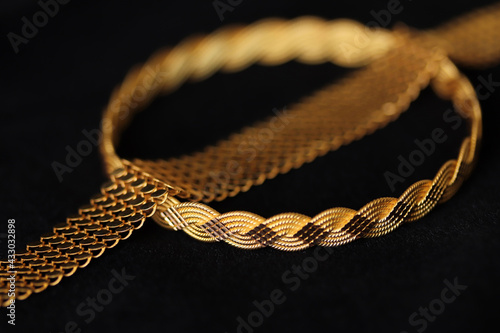 Tableau sur Toile gold bracelets on a black background
