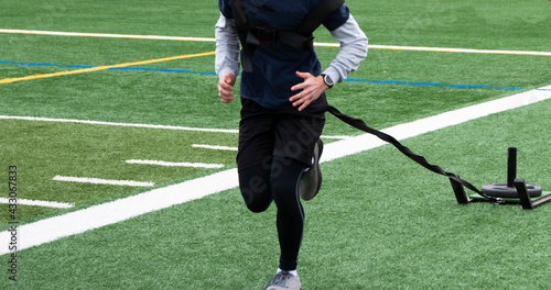 Tablou Canvas Close up of athlete pulling a sled carrying extra weight on a turf field