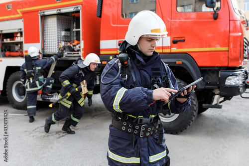 Photo Portrait of firefighter in fire fighting operation, fireman in protective clothing and helmet using tablet computer in action fighting