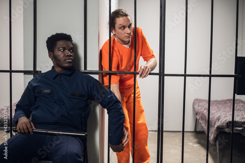 A prison guard passes a prisoner a cell phone through the bars Illegal contraband Fototapet