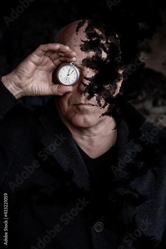 Fotografie, Obraz man holding a pocket watch to his eyes and black smoke