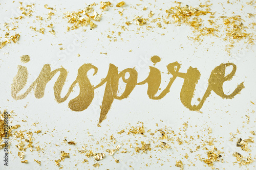 Inspire. Motivating lettering on white board. Handmade creativity. Gold letters. Gilding.