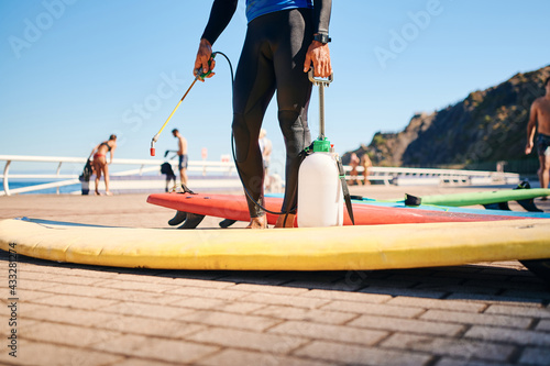 Fotografia unrecognizable surf instructor in neoprene disinfecting surfboards on the beach