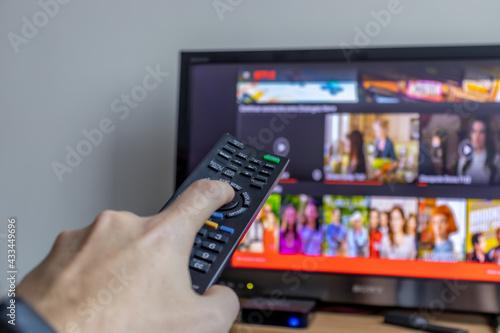 Wallpaper Mural Ligando televisão com controle remoto.