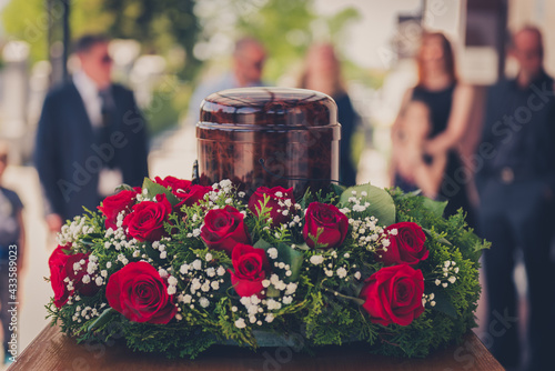 Canvastavla Funerary urn with ashes of dead and flowers at funeral.