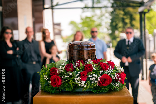 Fototapeta Funerary urn with ashes of dead and flowers at funeral.