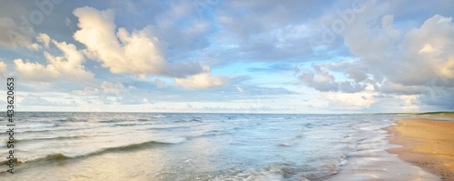 Photo Clear sky with glowing cumulus clouds above the Baltic sea shore after thunderstorm at sunset