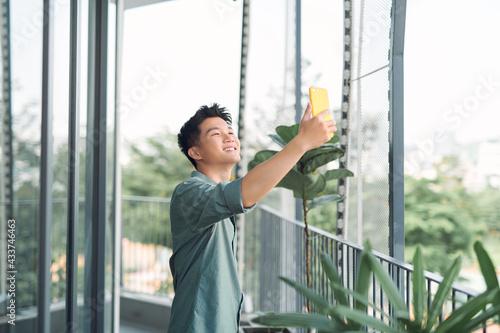 Valokuva Young asian man taking a selfie on balcony