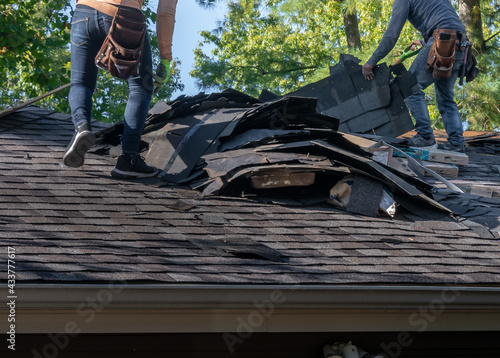 Roofers removing old material from a house in preparation for storm damage repair Fototapeta