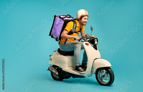 Fotografiet Young courier, delivery man in uniform with thermo backpack on a moped isolated on blue background