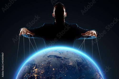 Fotografie, Obraz A man, a puppeteer, manipulates the planet