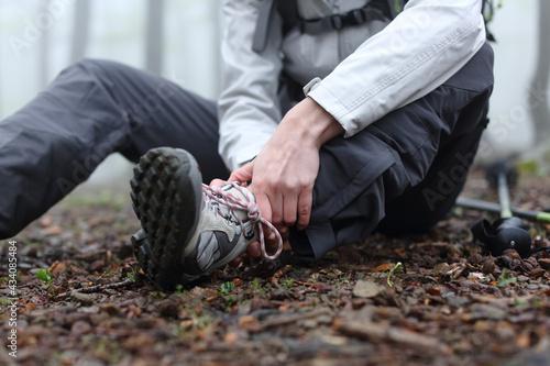 Fotografia, Obraz Trekker complaining alone in the mountain with broken ankle