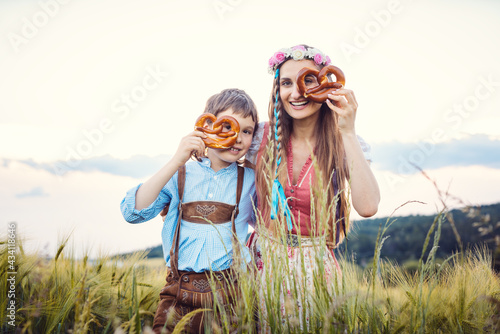 Fototapeta Mother and son in Bavaria looking through pretzels