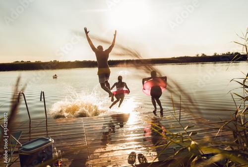 Canvas Print Friends having fun enjoying a summer day swimming and jumping at the lake