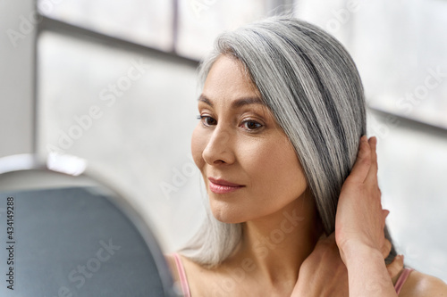 Stampa su Tela Portrait of beautyful happy middle aged mature asian woman, senior older 50s lady pampering touching gray hair looking at herself at mirror indoors