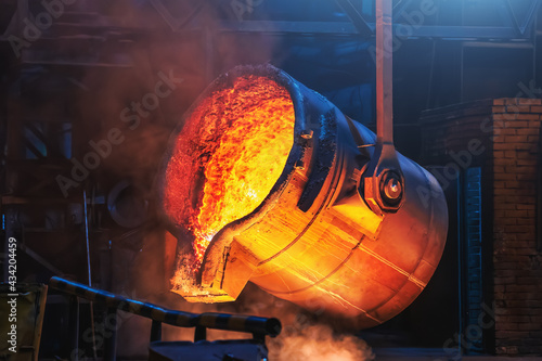 Fototapeta Big ladle container with molten liquid metal or iron in foundry close up