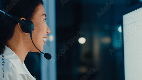 Canvastavla Millennial Asia young call center agent or customer support service executive using computer and microphone headset working technical support in late night office