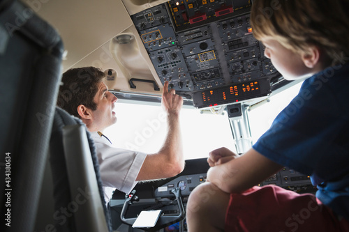 Leinwand Poster Male pilot explaining control panel to boy in airplane cockpit
