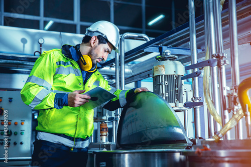 Fotografiet Factory worker engineer working in factory using tablet computer to check maintenance boiler water pipe in factory