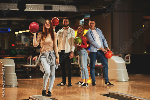 Leinwand Poster Beautiful group of young people posing in a bowling alley with a ball in their h