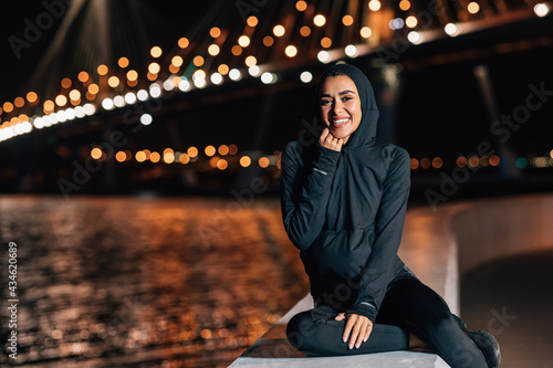 Photographie Beautiful middle east woman in hoodie sitting on embankment at night and resting