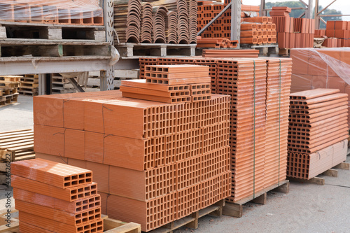 Pallets with stack of redbricks lying at warehouse of building materials in sunn Fototapeta