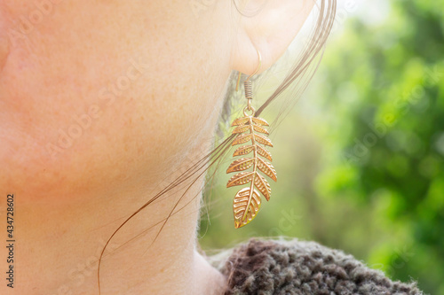 Outdoor detail of female ear wearing metal ornamental earring Fototapet