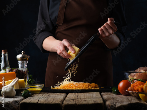 The chef prepares the ingredients for cooking baked duck with vegetables and grates cheese Poster Mural XXL