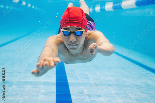 Photo portrait of paralympic Swimmer young latin man Underwater Training In Pool with