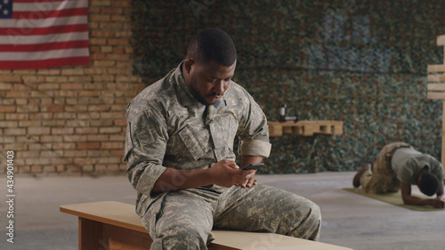 Foto Black military men using smartphone in gym together
