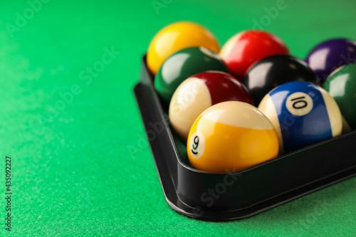 Fotografie, Obraz Billiard balls in triangle rack on green table, closeup