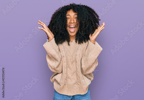 Young african american girl wearing casual clothes celebrating mad and crazy for success with arms raised and closed eyes screaming excited. winner concept