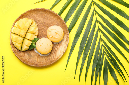 Plate with tasty mango ice cream and palm leaf on color background Fototapet