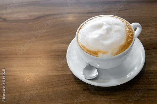 Leinwand Poster Hot coffee cappuccino latte spiral foam on dark wooden background, hot coffee wi