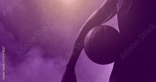 Composition of athletic male basketball player with ball over smoke