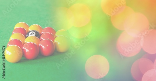 Composition of snooker balls on snooker table with orange and yellow spots in background