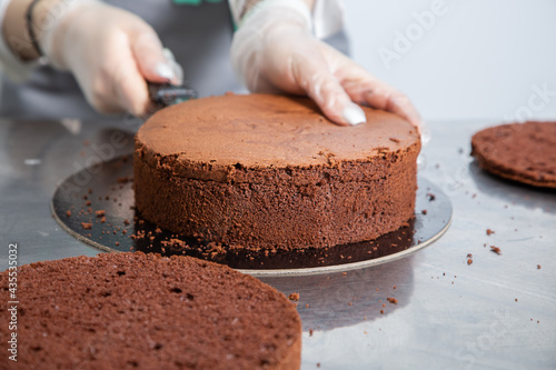Canvas Womans hands chef cutting chocolate cake layers and stacking them on metal table