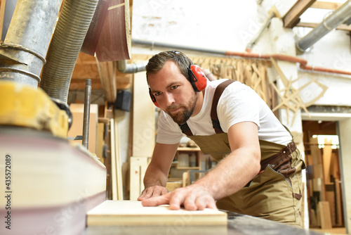 carpenter works in a joinery - workshop for woodworking and sawing Fototapet