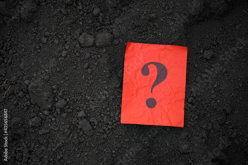 Fotografia, Obraz A red paper note with a question mark on it lying on soil